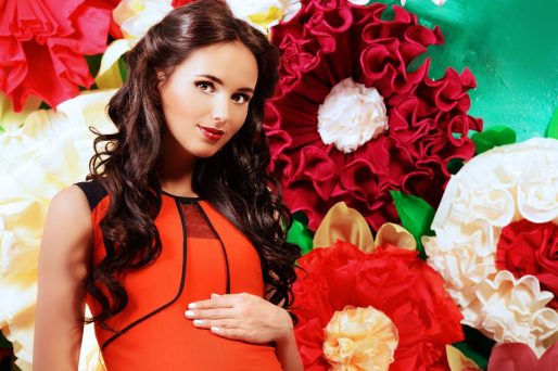 Close-up portrait of a beautiful pregnant woman posing over big bright flowers. Clothes for pregnant women. Beauty, fashion.