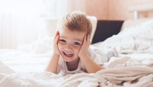 niño en la cama riendo