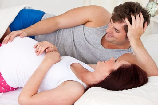 cute man touching the belly of his pregnant wife lying on the bed at home during the morning