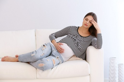 Mujer semi acostada con la mano en su frente- Dolor lumbar