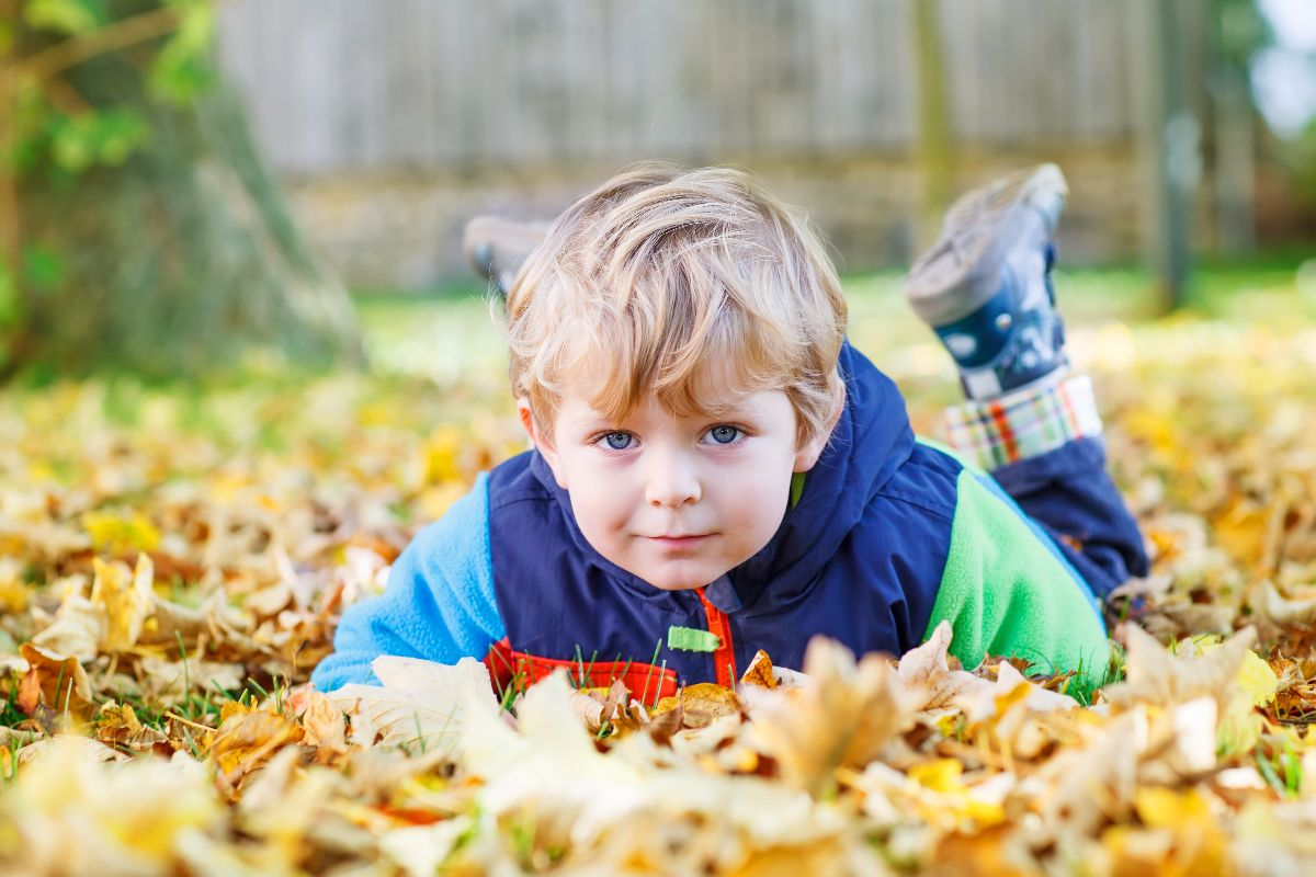 niño tirado hojas