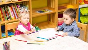 niños sentados en una mesa, con cuadernos y colores.