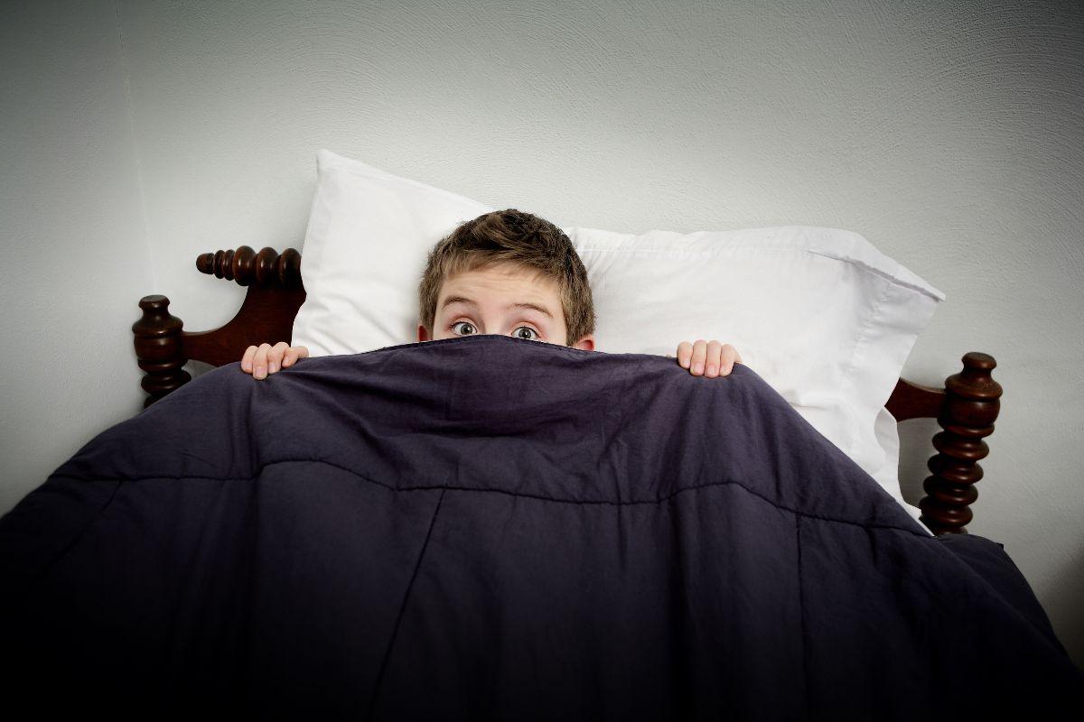 niño en la cama con miedo