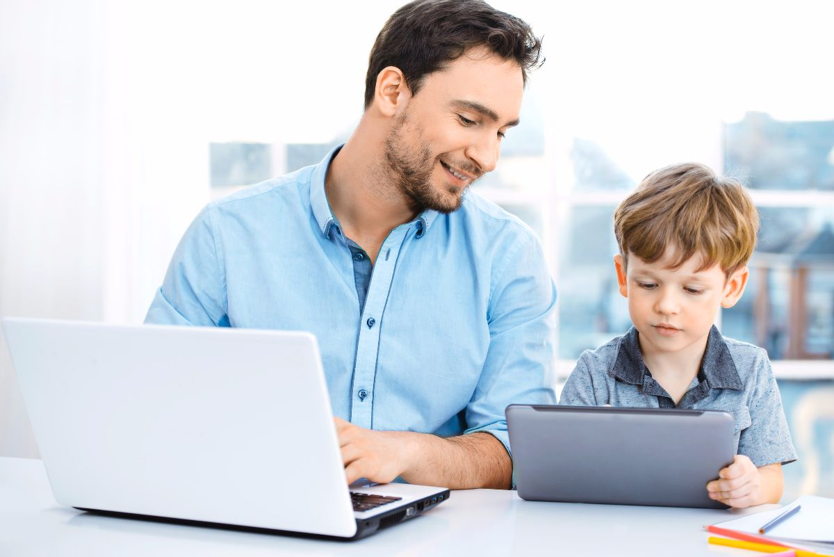 Nice family photo of little boy and his father. Boy and dad sitting at room with big window. Young man working with laptop while boy using tablet computer
