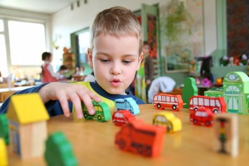 Niño jugando con los juguetes del Jardín Infantil