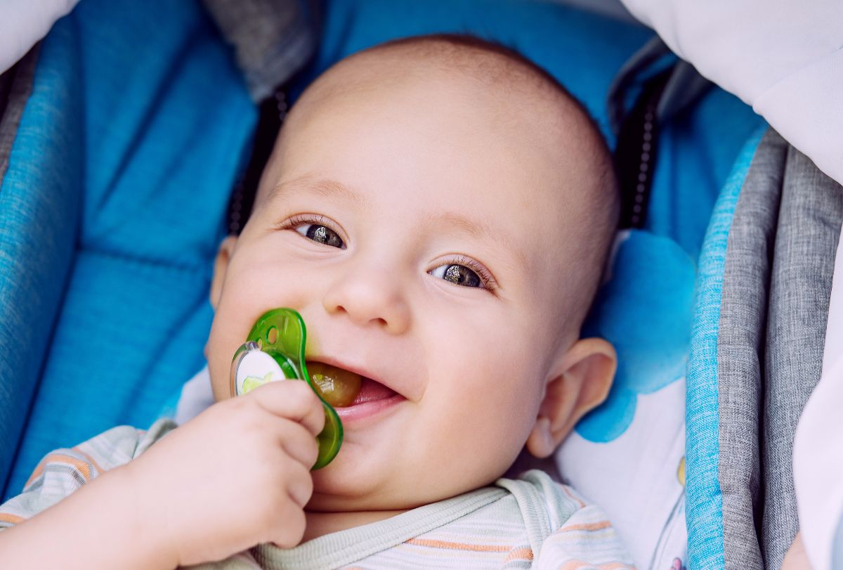 happy baby with pacifier lying in a stroller ** Note: Soft Focus at 100%, best at smaller sizes