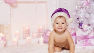 Christmas Baby in Santa Hat Kid in Decorated Xmas Pink background Child one year old looking at camera