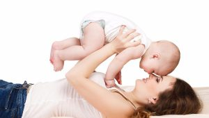 Mom, smiling, doing exercises and massages with their little baby lying on a fluffy beige carpet in the room on the floor,lifting her son in her arms, isolated on white background.