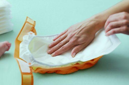 pañal y mano de una mujer- Mi bebé no defeca diariamente, ¿Es normal?